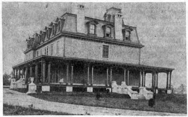 View of original Louella House, home of the Henry Askin family, which was completed in 1869 after having been under construction for one year. This picture shows the west side of the building, with a partial view of the grounds on the east side. The elevation to the right in the picture contains the gas retorts that supplied the building. (A man is shown standing at the entrance to this underground chamber.)
