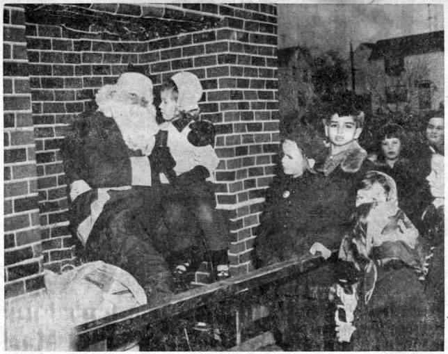 Little Susan Jones makes sure that Santa Claus (William Fanus) knows what she wants for Christmas, as she sits under the fireplace with Old St. Nick while other children from the Wayne Terraces area look on. The photo was taken just after Santa's unusual arrival on the Radnor Fire Company ladder truck on Saturday. (Photo by Stellabott Studio)